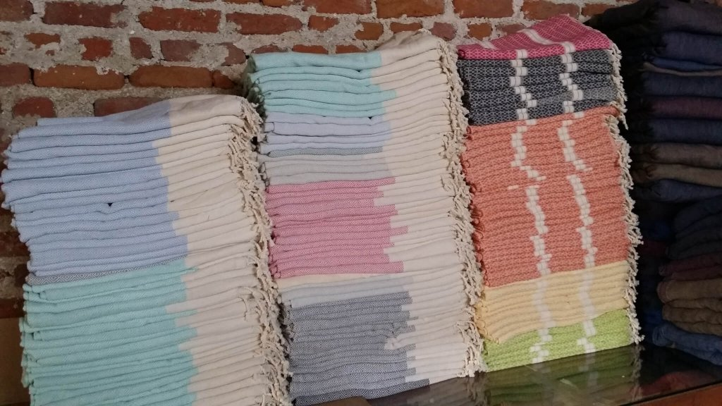 Three stacks of brightly coloured peshtemal hammam towels